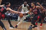 Boston Celtics guard Jaylen Brown (7) tries to thread between Chicago Bulls guard Tomas Satoransky (31) and forward Daniel Gafford (12) on a drive to the basket during the first half of an NBA basketball game in Boston, Monday, Jan. 13, 2020. (AP Photo/Charles Krupa)