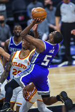 Sacramento Kings guard De'Aaron Fox (5) is fouled on his way to the basket by Atlanta Hawks forward De'Andre Hunter (12) during the fourth quarter of an NBA basketball game in Sacramento, Calif., Wednesday, March 24, 2021. (AP Photo/Hector Amezcua)