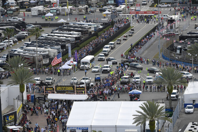 Fans form long lines to enter the infield before the NASCAR Daytona 500 auto race at Daytona International Speedway, Sunday, Feb. 16, 2020, in Daytona Beach, Fla. Additional Secret Service screening is required for the sold-out crowd, due to the attendance of President Donald Trump. (AP Photo/Phelan M. Ebenhack)