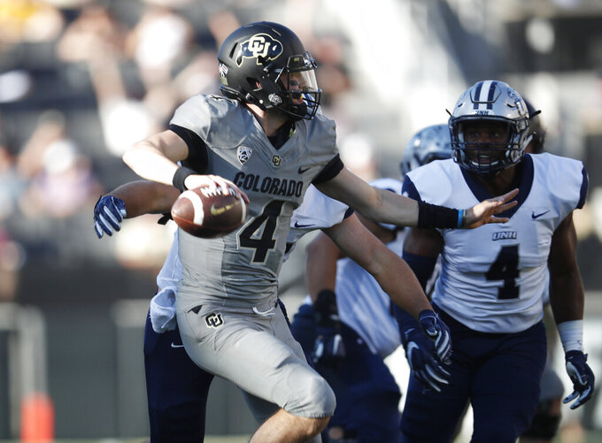 FILE - In this Sept. 15, 2018, file photo, Colorado quarterback Sam Noyer ooks to pass the ball under pressure from New Hampshire defensive end Josh Kania, back left, and linebacker Quinlen Dean during the second half of an NCAA college football game. Colorado hosts UCLA to open the team's home schedule for the PAC-12 season. (AP Photo/David Zalubowski, File)