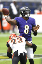 Cincinnati Bengals cornerback Darius Phillips (23) applies a hit as Baltimore Ravens quarterback Lamar Jackson (8) throws a pass during the first half of an NFL football game, Sunday, Oct. 11, 2020, in Baltimore. (AP Photo/Nick Wass)