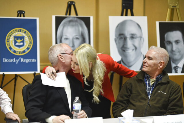 Abuse survivor Robert Stone, left, gets a hug from Attorney Sarah Klein as JP DesCamp looks on as the men have accused former University of Michigan doctor Robert E. Anderson of systematic sexual assault as they speak to the news media in Ypsilanti, Mich., on Thursday, March 5, 2020. (Max Ortiz/Detroit News via AP)