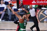 Boston Celtics' Jayson Tatum (0) celebrates dunking in front of Miami Heat's Kendrick Nunn, rear, during the second half of an NBA conference final playoff basketball game, Saturday, Sept. 19, 2020, in Lake Buena Vista, Fla. (AP Photo/Mark J. Terrill)