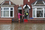 People cope with flood water on a residential street in Doncaster, England, as parts of England endured heavy rain, with some scores of people rescued or forced to evacuate their homes, and travel plans thrown into chaos, Friday Nov. 8, 2019. Torrential rain has drenched parts of north and central England, forcing some to evacuate their homes and stranding a small group of people in a shopping centre overnight. (Danny Lawson/PA via AP)