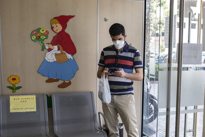 36 year-old Vasilis Tsipiras waits to receive his first dose of the of the AstraZeneca COVID-19 vaccine, at a vaccination center in Piraeus, near Athens, Thursday, April 29, 2021. Greece's health minister says any adult who wants to be vaccinated against COVID-19 will be able to do so by the end of June, as the country ramps up its vaccination drive. (AP Photo/Petros Giannakouris)