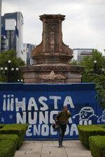 A pedestrian walks past graffiti that reads in Spanish