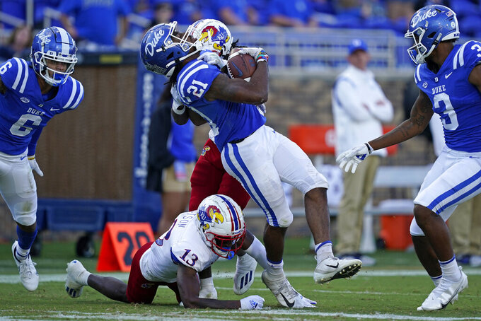 Duke running back Mataeo Durant (21) runs the ball while Kansas cornerback Ra'Mello Dotson (13) tackles during the second half of an NCAA college football game in Durham, N.C., Saturday, Sept. 25, 2021. (AP Photo/Gerry Broome)