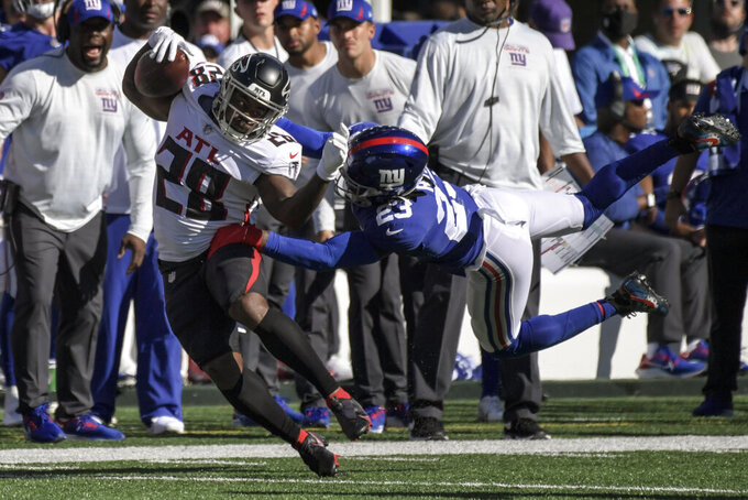 Atlanta Falcons running back Mike Davis (28) is tackled by New York Giants cornerback Logan Ryan (23) during the second half of an NFL football game, Sunday, Sept. 26, 2021, in East Rutherford, N.J. (AP Photo/Bill Kostroun)