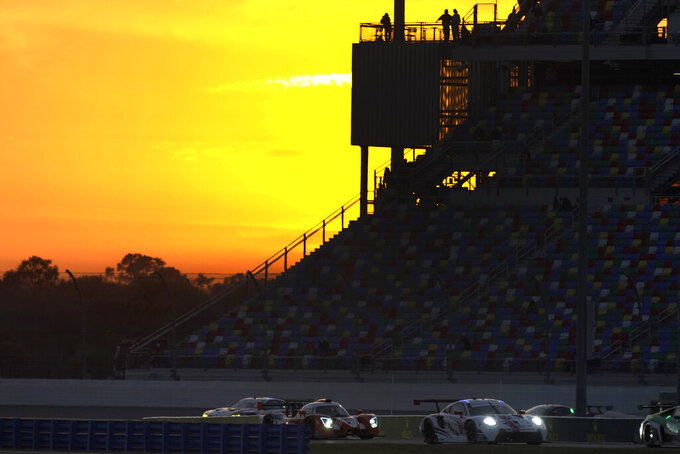Cars navigate the infield road course as the sun sets during the Rolex 24 hour auto race at Daytona International Speedway, Saturday, Jan. 30, 2021, in Daytona Beach, Fla. (AP Photo/John Raoux)