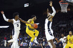 Marquette's Markus Howard, center, splits through the defense of Providence's David Duke (3) and Nate Watson (0) to make a basket during the first half of an NCAA college basketball game Saturday, Feb. 22, 2020, in Providence, R.I. (AP Photo/Stew Milne)