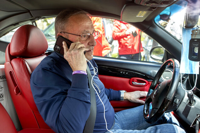 Former Gov. Paul LePage, sitting in a Lexus SC 430, uses his cell phone to address protesters rallying against the executive orders by Gov. Janet Mills to keep some Maine businesses closed to help prevent the spread of coronavirus, Saturday, May 16, 2020, in Augusta, Maine. His call was broadcast over speakers set up at the nearby rally. LePage, now a resident of Florida, stayed in his car parked near the rally. A speaker at the event said the former governor was quarantining. (AP Photo/Robert F. Bukaty)