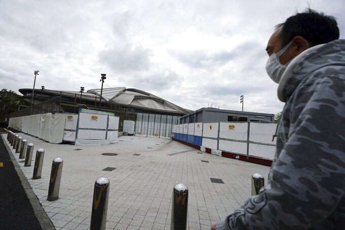 A man wearing a protective mask to help curb the spread of the coronavirus walks near Tokyo Metropolitan Gymnasium, one of venues for the postponed Tokyo 2020 Olympics Tuesday, April 6, 2021, in Tokyo. Many preparations are still up in the air as organizers try to figure out how to hold the postponed games in the middle of a pandemic. (AP Photo/Eugene Hoshiko)