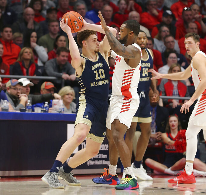 George Washington's Jamison Battie (10) is defended by Dayton's Trey Landers (3) during the first half of an NCAA college basketball game Saturday, March 7, 2020, in Dayton, Ohio. (AP Photo/Tony Tribble)