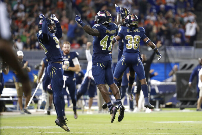 FIU defensive lineman Noah Curtis, left, and linebacker Chris Whittaker (47) celebrate after their team stopped Miami on fourth down during the first half of an NCAA college football game, Saturday, Nov. 23, 2019, in Miami. (AP Photo/Lynne Sladky)