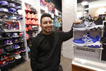 Victor Duran, a co-manager of a sports apparel store at the Southcenter mall, south of Seattle, poses for a photo at the store, Wednesday, Dec. 11, 2019, in Tukwila, Wash. Duran, 23, said he makes about $52,000 a year and doesn't get overtime, but is required to work at least 45 hours per week, and up to 60 during the holidays. Duran is one employee who could benefit from new overtime rules in Washington state, which will allow hundreds of thousands of workers who have been exempt to begin collecting when they work more than 40 hours per week. (AP Photo/Elaine Thompson)