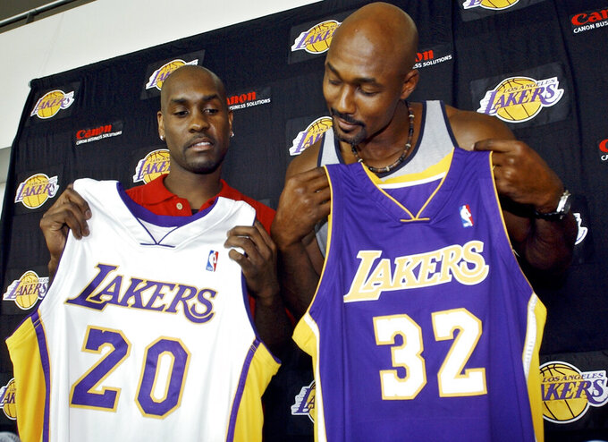 FILE - In this July 17, 2003 file photo Gary Payton, left, and Karl Malone display their new Los Angeles Lakers' jerseys during a news conference at the Staples Center in Los Angeles. The two players signed with the Lakers as free agents. Tom Brady's departure from the New England Patriots on Tuesday, March 17, 2020, brings an end to one of the NFL's most memorable eras. That's happened plenty of times before in sports — a legendary star switching teams toward the end of his career. Malone was hoping for a triumphant ending when he signed with the Lakers in 2003 after 18 stellar seasons in Utah. But he came up just short in his quest for a title when the Lakers lost to Detroit in the 2004 NBA Finals. (AP Photo/Ric Francis, file)