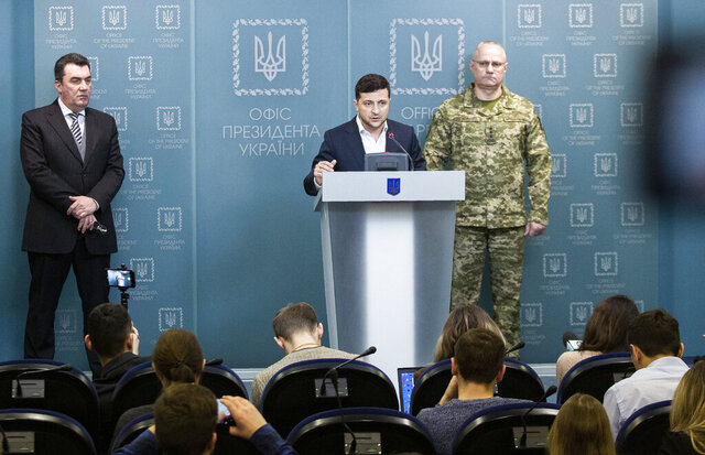 In this handout photo provided by the Ukrainian Presidential Press Office, Ukrainian President Volodymyr Zelenskiy speaks to media at a briefing after the Security Council meeting in Kyiv, Ukraine, Tuesday, Feb. 18, 2020. Ukraine and Russia-backed separatists are blaming each other for an outbreak of fighting in the country's rebel-held east. Ukraine's Army Chief of Staff Ruslan Homchak, right, and the Secretary of the National Security and Defense Council Oleksiy Danilov, left, listen. (Ukrainian Presidential Press Office via AP)