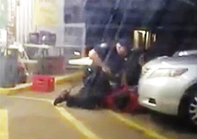 FILE - In this July 5, 2016, image made from video provided by Arthur Reed, Alton Sterling, in red, is restrained by two Baton Rouge police officers, one holding a gun, outside a convenience store in Baton Rouge, La. Moments later, one of the officers shot and killed Sterling, a black man who had been selling CDs outside the store, while he was on the ground. Howie Lake II, a white Louisiana police officer who assisted in the arrest in which Sterling was fatally shot, was dismissed Monday, Sept. 21, 2020, from a wrongful death lawsuit. (Arthur Reed via AP, File)
