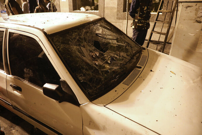 A car's windshield is shattered by a wave of the explosion of the Sina Athar Clinic in Tehran, Iran, early Wednesday, July 1, 2020. Iranian state TV says an explosion from a gas leak in the medical clinic in northern Tehran has killed multiple people. (AP Photo/Vahid Salemi)