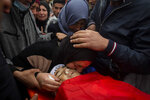 Relatives mourn the body of a 13-year-old Ali Abu Alia who was shot dead by Israeli military forces during clashes with a stone-throwing Palestinains during his funeral in al-Mughair village near the West Bank city of Ramallah, Saturday, Dec. 5, 2020. (AP Photo/Majdi Mohammed)