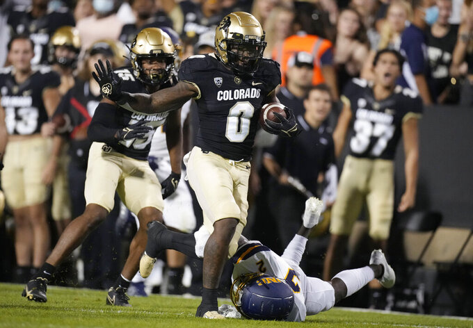 Colorado running back Ashaad Clayton runs past Northern Colorado defensive back Greg Laday during the second half of an NCAA college football game Friday, Sept. 3, 2021, in Boulder, Colo. Colorado won 35-7. (AP Photo/David Zalubowski)