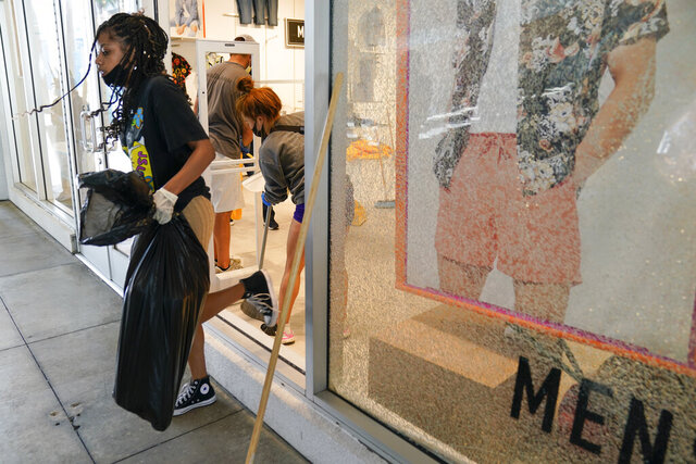 Alycia Barber carries a trash bag through a broken window at Forever 21 at The Pike Outlets on Monday, June 1, 2020, in Long Beach after overnight protests over the death of George Floyd . Floyd died in police custody on Memorial Day in Minneapolis. (AP Photo/Ashley Landis)
