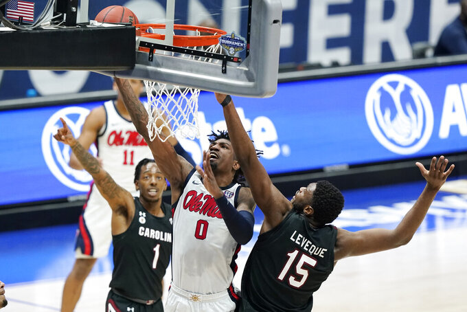 Mississippi's Romello White (0) scores against South Carolina's T.J. Moss (1) and Wildens Leveque (15) in the first half of an NCAA college basketball game in the Southeastern Conference Tournament Thursday, March 11, 2021, in Nashville, Tenn. (AP Photo/Mark Humphrey)