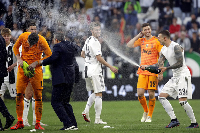 Juventus players celebrate at the end of a Serie A soccer match between Juventus and AC Fiorentina, at the Allianz stadium in Turin, Italy, Saturday, April 20, 2019. Juventus clinched a record-extending eighth successive Serie A title, with five matches to spare, after it defeated Fiorentina 2-1. (AP Photo/Luca Bruno)