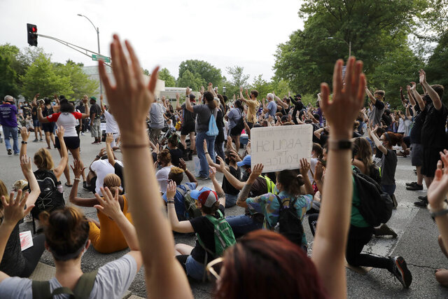 Protesters raise their arms as they block an intersection while bringing attention to racial injustice, Friday, July 3, 2020, in St. Louis. (AP Photo/Jeff Roberson)