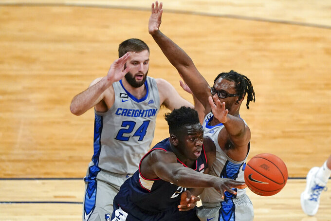 Connecticut's Adama Sanogo (21) passes the ball away from Creighton's Mitch Ballock (24) and Denzel Mahoney during the first half of an NCAA college basketball game in the semifinals in the Big East men's tournament Friday, March 12, 2021, in New York. (AP Photo/Frank Franklin II)