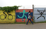 A man walks past sports murals originally painted on a wall as promotional tools for the 2018 Asian Games in Jakarta, Indonesia, Tuesday, Feb. 19, 2019. Indonesia has officially joined bidding to host the 2032 Olympics following its success staging the Asian Games last year, the deputy chairman of its national Olympic committee said Tuesday, highlighting the rising ambitions of the giant but perennially underperforming Southeast Asian nation. (AP Photo/Dita Alangkara)