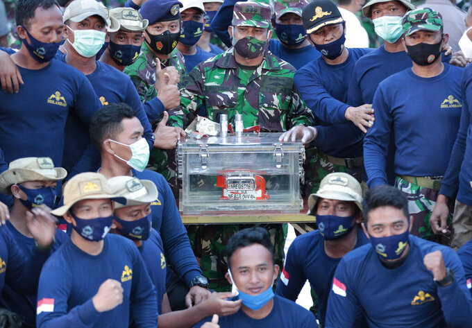 Indonesian Navy personnel pose for photos with the flight data recorder recovered from the wreckage of Sriwijaya Air flight SJ-182 in the Java Sea at Tanjung Priok Port, Tuesday, Jan. 12, 2021. Indonesian navy divers searching the ocean floor on Tuesday recovered the flight data recorder from a Sriwijaya Air jet that crashed into the Java Sea with 62 people on board, Saturday, Jan. 9, 2021. (AP Photo/Dita Alangkara)