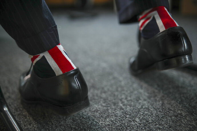 British European Parliament member Nigel Farage wears socks with the Union flag as he speaks to a journalist during an interview at the European Parliament in Brussels, Tuesday, Jan. 28, 2020. With the Brexit moment set for Friday at midnight Brussels time, UK parliamentarians are packing boxes and removing personal items from their Brussels offices. (AP Photo/Francisco Seco)