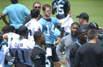 Carolina Panthers quarterback Sam Darnold, center, speaks with a teammate during a break in drills at the team's OTA  football practice on Tuesday, May 25, 2021 in Charlotte, N.C. (Jeff SIner/The Charlotte Observer via AP)