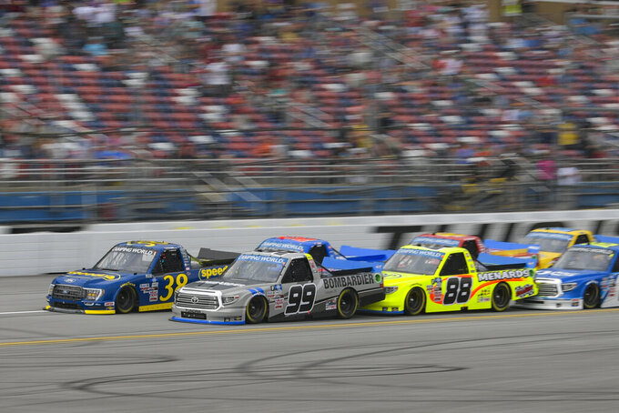 Ben Rhodes (99) and Todd Gilliland run side by side during the NASCAR Truck Series auto race Saturday, Oct. 2, 2021, in Talladega, Ala. (AP Photo/John Amis)