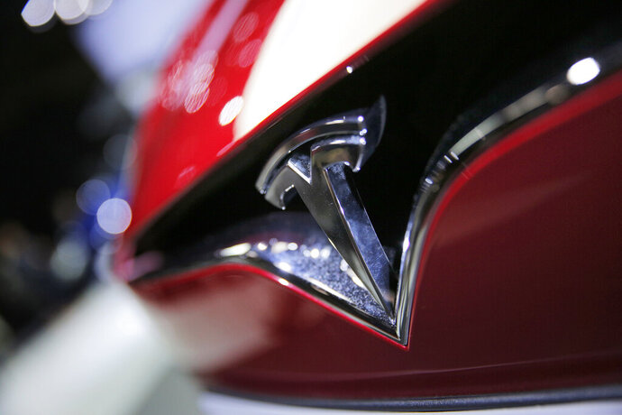 FILE- This Sept. 30, 2016, file photo shows the logo of the Tesla model S at the Paris Auto Show in Paris, France.  The U.S. government's auto safety agency is looking into allegations that all three of Tesla's electric vehicles can suddenly accelerate on their own. An unidentified person petitioned the National Highway Traffic Safety Administration asking for an investigation into the problem. The agency says the allegations include about 500,000 Tesla Model 3, Model S and Model X vehicles from the 2013 through 2019 model years. (AP Photo/Christophe Ena, File)