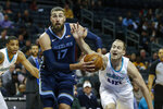 Charlotte Hornets center Cody Zeller, right, reaches in to strip the ball from Memphis Grizzlies center Jonas Valanciunas in the first half of an NBA basketball game in Charlotte, N.C., Wednesday, Nov. 13, 2019. (AP Photo/Nell Redmond)