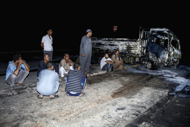 People stand near burned vehicles following a fire that broke out in the Shuqair-Mostorod crude oil pipeline, on the Cairo-Ismailia road, in Egypt, Tuesday, July 14, 2020. A ruptured crude oil pipeline set off a monstrous blaze on a desert highway in Egypt on Tuesday, injuring at least 17 people, local authorities said. (AP Photo/Alaa Ahmed)