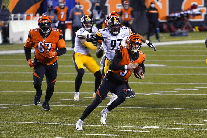 Cincinnati Bengals quarterback Ryan Finley (5) scrambles during the first half of an NFL football game against the Pittsburgh Steelers, Monday, Dec. 21, 2020, in Cincinnati. (AP Photo/Bryan Woolston)