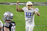Los Angeles Chargers quarterback Justin Herbert (10) celebrates after running back Kalen Ballage scored a touchdown against the Las Vegas Raiders during the second half of an NFL football game, Thursday, Dec. 17, 2020, in Las Vegas. (AP Photo/Isaac Brekken)