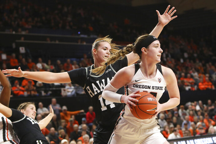 Oregon State's Kennedy Brown (42) passes the ball away from Hawaii's Lauren Rewers (14) during the first half of an NCAA college basketball game in Corvallis, Ore., Friday, Dec. 6, 2019. (AP Photo/Amanda Loman)