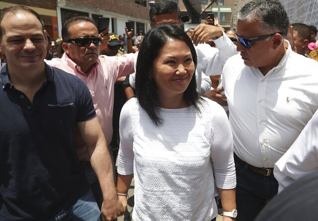 Keiko Fujimori, the daughter of Peru's former President Alberto Fujimori, and leader of the opposition party, center, with her husband Mark Vito Villanela, left, arrive to vote during congressional elections in Lima, Peru, Sunday, Jan. 26, 2020. Peruvians are voting to elect 130 new members of the congress that will legislate for only one year in place of the congress that was dissolved by president Martin Vizacarra in September 2019. (AP Photo/Martin Mejia)