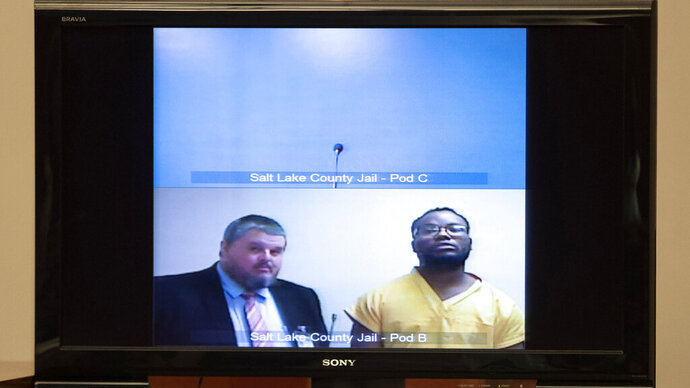 Attorney Neal Hamilton, left, stands with Ayoola A. Ajayi during his video preliminary hearing at the Matheson Courthouse Monday, July 15, 2019, in Salt Lake City. Ajayi, a tech worker charged in the death of a Utah college student, appeared by video from jail alongside a court-appointed attorney during a quick hearing to set a future court date. He did not speak or enter a plea to murder, kidnapping and other charges. (Steve Griffin/Deseret News, via AP Photo, Pool)