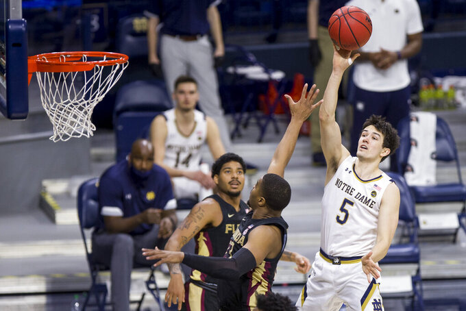 Notre Dame's Cormac Ryan (5) goes up for a shot as Florida State's RayQuan Evans, left, and M.J. Walker, center, defend during the second half of an NCAA college basketball game Saturday, March 6, 2021, in South Bend, Ind. Notre Dame won 83-73. (AP Photo/Robert Franklin)