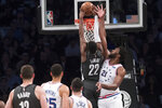 Brooklyn Nets guard Caris LeVert (22) dunks past Philadelphia 76ers center Joel Embiid (21) during the first half of Game 4 of a first-round NBA basketball playoff series, Saturday, April 20, 2019, in New York. (AP Photo/Mary Altaffer)