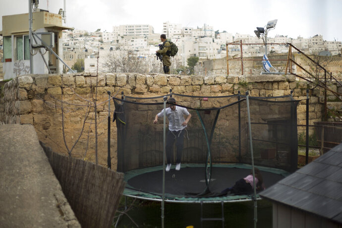 FILE - In this March 7, 2019, file photo, settlers jump on a trampoline as an Israeli solider stands guard in the Israeli controlled part of the West Bank city of Hebron. Israel's premier human rights group has begun describing both Israel and its control of the Palestinian territories as a single