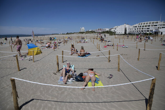 Sunbathers lie in an area marked to enforce social distancing measures in La Grande Motte, southern France, Sunday, May 24, 2020. Grateful French families flocked to the beach at La Grande Motte on the Mediterranean shore Sunday, swimming and sunbathing in areas carefully marked to keep them a safe distance from others. (AP Photo/Daniel Cole)