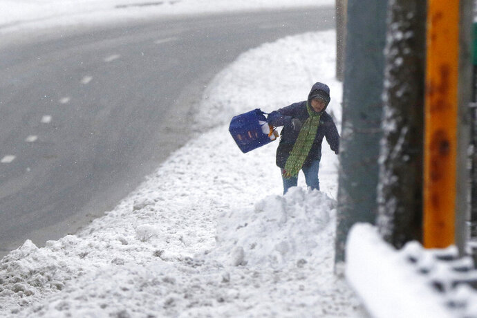 A pedestrian walks through deep snow after an overnight snowfall, Monday, Dec. 2, 2019, in Marlborough, Mass. (AP Photo/Bill Sikes)