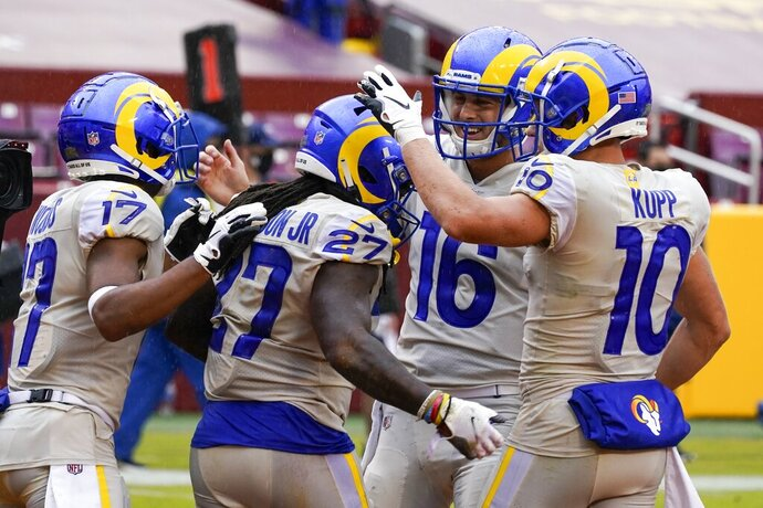 Los Angeles Rams' Darrell Henderson (27) is congratulated after runnig for a touchdown during the second half of an NFL football game against the Washington Football Team Sunday, Oct. 11, 2020, in Landover, Md. (AP Photo/Steve Helber)