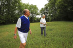 Carol McCloskey, right, of Newtown Square, and her husband, J.R. Delich, left, look over a plot of land she owns in the Brandywine Valley in Chester County, Pa., on Thursday, June 3, 2021. McCloskey has owned a half acre plot on what's known as Indian Knoll and designated by the county as a historical Native American burial site of the Lenape. Now planning her estate, she wants to donate the property, preferably to Native Americans, to ensure its preservation. (David Maialetti/The Philadelphia Inquirer via AP)